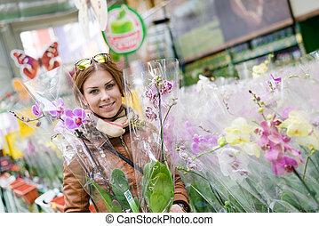 trevlig, kvinna räcka, en, orkidé, in, räcker, le, betrakta kamera, in, a, supermarket