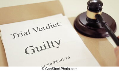 Trial verdict folder with gavel placed on desk of judge in court
