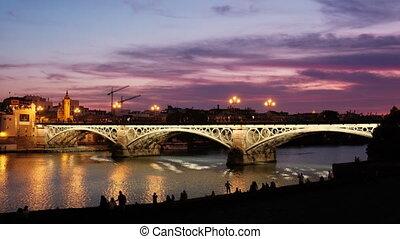 The Triana Bridge, Or Puente De Isabel II, over the Guadalquivir River in Seville, Spain, At Dusk.