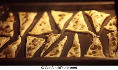 Triangles of puff pastry inside oven, baking tray inflate...