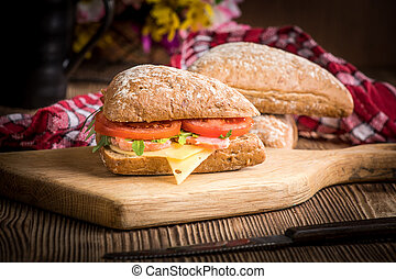 Triangular sandwich with cheese, ham and tomato.