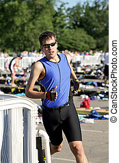 Triathlon - Triathlete exits the transition area to begin...