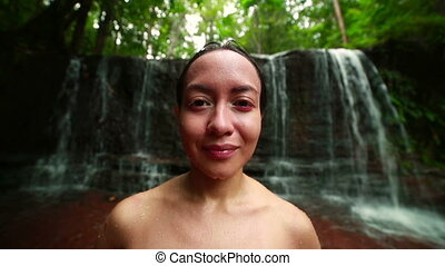 Tribal girl in jungle waterfall