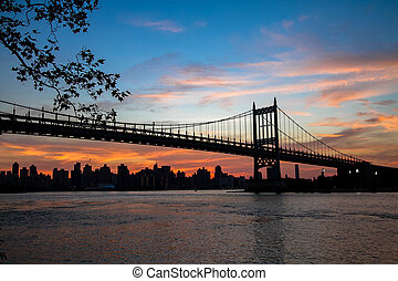 Triborough bridge over the river and buildings in silhouette and sunset sky