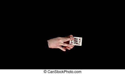 Trick of magician with cards, taking card from nowhere on black