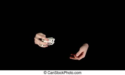 Trick of magician with cards, throwing cards on black -...