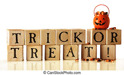 "Rustic alphabet blocks arranged to say, ""Trick or Treat!"" A pumpkin-bucket overflowing with candy corn sits on top. Isolated on white."