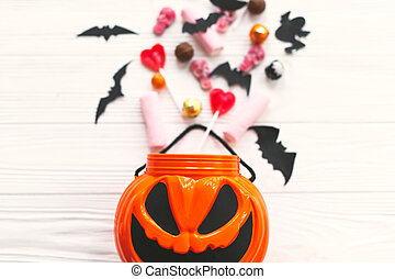 Trick or treat. Halloween candy spilled from jack o lantern bucket with skulls, black bats, ghost, spider decorations on white wooden background, flat lay. Halloween sweets. Copy space.