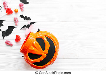 Trick or treat. Halloween candy spilled from jack o lantern bucket with skulls, black bats, ghost, spider decorations on white wooden background. Halloween sweets. Copy space.