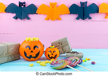 Trick or Treat - Halloween jack o' lantern, candy and rainbow lollipop on pink and blue wooden background with copy space for text. Flat lay, top view