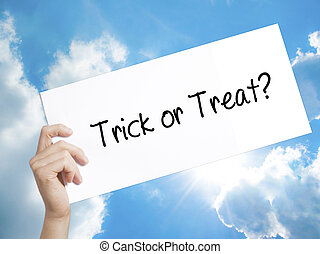 Trick or Treat? Sign on white paper. Man Hand Holding Paper with text. Isolated on sky background.