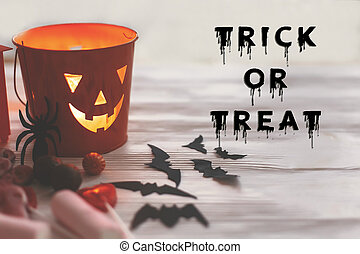 Trick or treat text, bloody sign. Happy Halloween. Jack o Lantern bucket with holiday candy, bats, spiders, skulls on white rustic wooden background. Season's greeting card