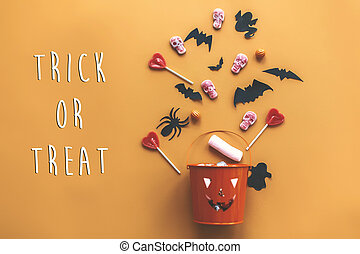 Trick or treat text sign. Happy Halloween. Jack o Lantern bucket with holiday candy, bats, spiders, skulls on orange paper, flat lay. Space for text. Season's greeting card