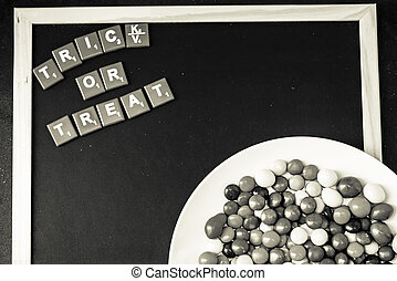 Trick or Treat word on blackboard with colorful chocolate candy