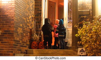 Trick or treating in Halloween nigh - Three children in...