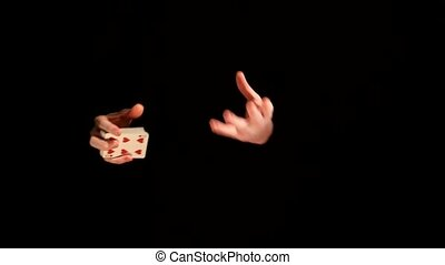 Trick with playing card on black background - Magician...