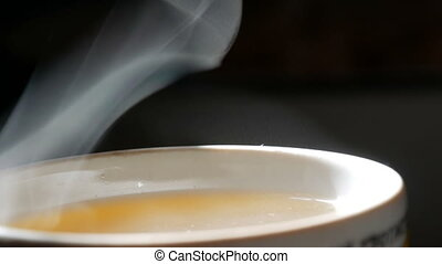 Trickle of Steam Slowly Rising from the Cup of tea close up...