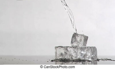 Trickle of water in a super slow motion flowing on ice cubes