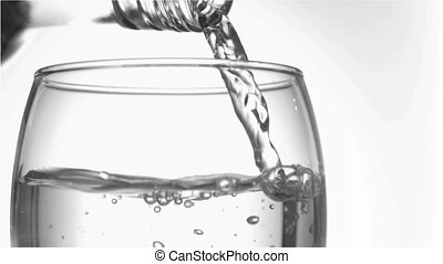 Trickle of water in a super slow motion finishing to serve of the glass bottleneck in a tumbler glas