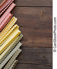 Tricolor mafalde pasta on the old wooded table