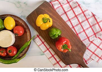 Tricolor peppers on a wooden board. Top view