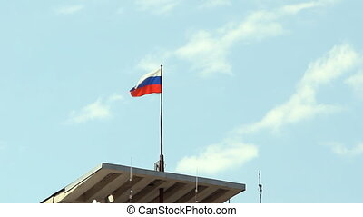 Tricolor Russian flag fluttering in the wind over blue sky