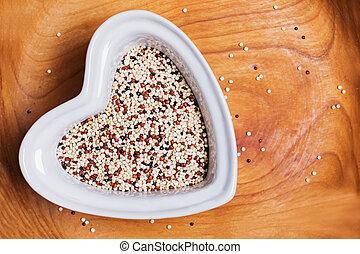 Tricolour quinoa grain super food in heart shaped bowl, top view.