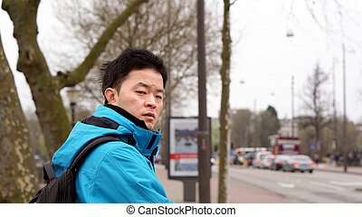 Tried, jet lag Asian man after traveling to Europe