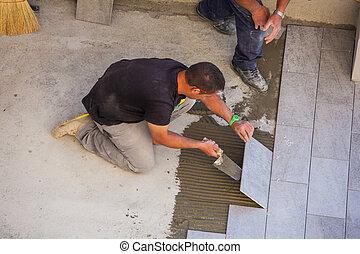 Worker Installing ceramic floor tiles - TRIESTE, ITALY -...