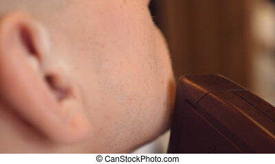 Trimming beard of male client with clipper at barber shop....