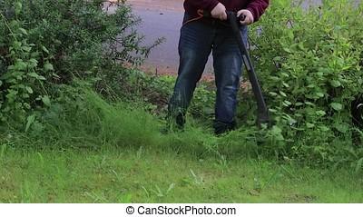 trimming garden weeds around yard - using weed trimmer to...