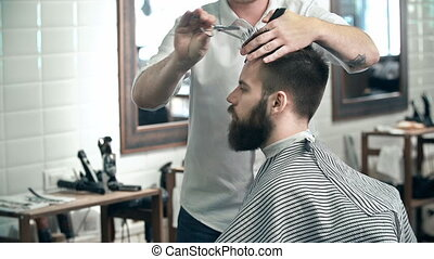 Trimming Hair - Over shoulder view of trendy guy having his...