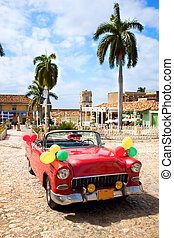 Red oldtimer car in the central square of Trinidad