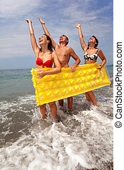 trio, de, jovens, divirta, ligado, seacoast, e, ter, amarela, inflável, mattress., grupo juventude, tem, descanso, ligado, praia., sujeito, e, duas meninas, levantar, praia, tendo, levantado, hands.