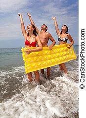 trio, gens, gonflable, soulevé, jaune, jeune, mattress., avoir, groupe, filles, deux, à terre, a, littoral, plage., repos, prise, hands., jeunesse, stand, amusement, type, avoir