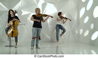 Trio girls playing the violins one on the cello in the white...