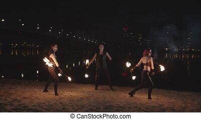 Trio of artists dancing with lit staves at night - Beautiful...