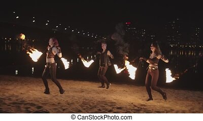 Skillful trio of artists performing amazing sight of fireshow poing on river bank in lights of night city. Attractive firegirls and man spinning burning poi mesmerizing with fire art at dusk.