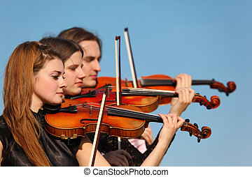 trio of violinists plays against sky