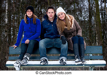 trio sitting on a parkbench in winter - 3 friends sitting on...