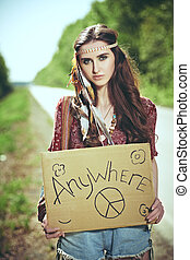 trip to anywhere - Beautiful hippie girl hitchhiking along a...