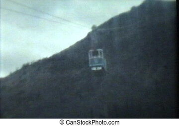 A young family takes a gondola cable car ride up the side of a mountain to view the beautiful surroundings while on their summer vacation. (Scan from archival 8mm film)