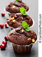 Triple chocolate muffins with cranberries on black stone background