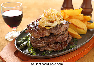 Grilled triple decker rib fillet steak with fried chips ready to serve.