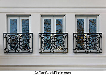 Three elegant windows with brass railings reflecting blue sky and trees