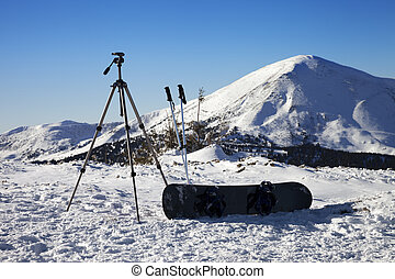 Tripod for photography camera, ski poles, snowboard on snow in mountains
