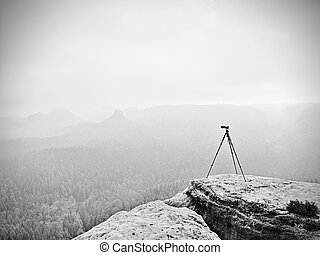 Tripod on the peak ready for photogrpahy. Exposed rocky view point. Misty rainy autumnal day