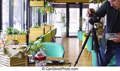 Tripod shot of man using digital camera and making photos of...