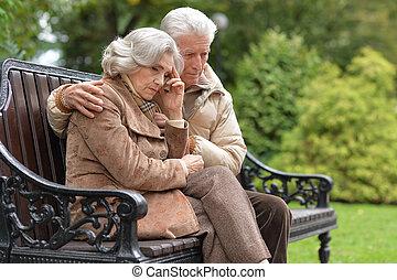 trist, elderly kopplar ihop, sittande, på, a, bänk, in, höst, parkera