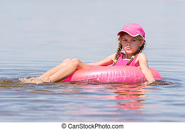 triste, menina, em, um, boné, flutuante, em, a, rio, sentado, ligado, a, natação, círculo